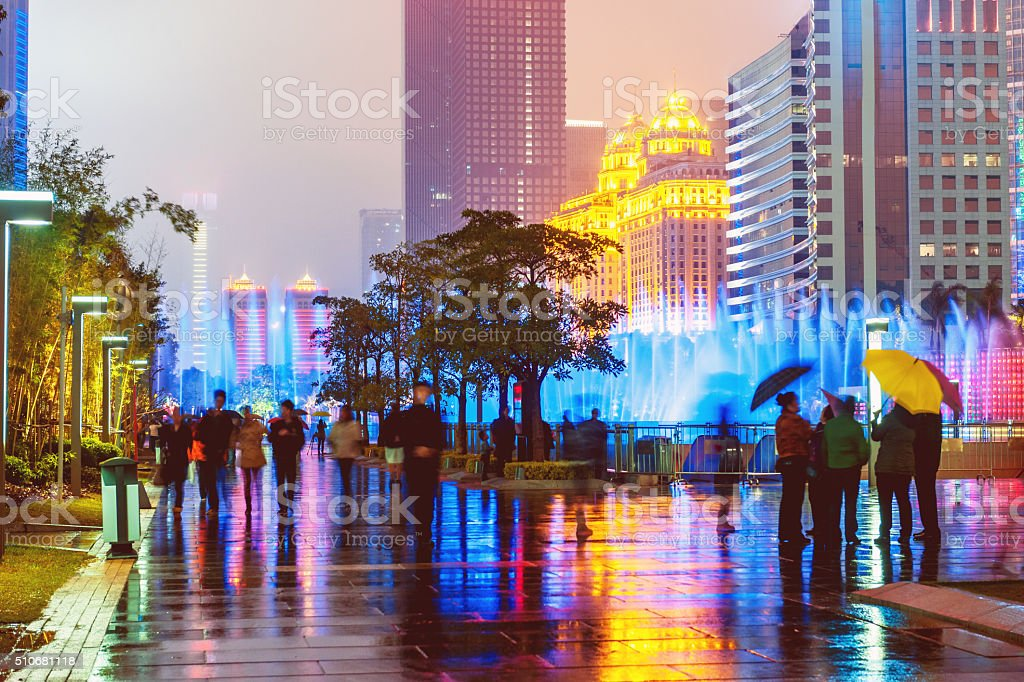 Guangzhou Office Buildings,people abstract,,umbrellas,fountain,night, China stock photo