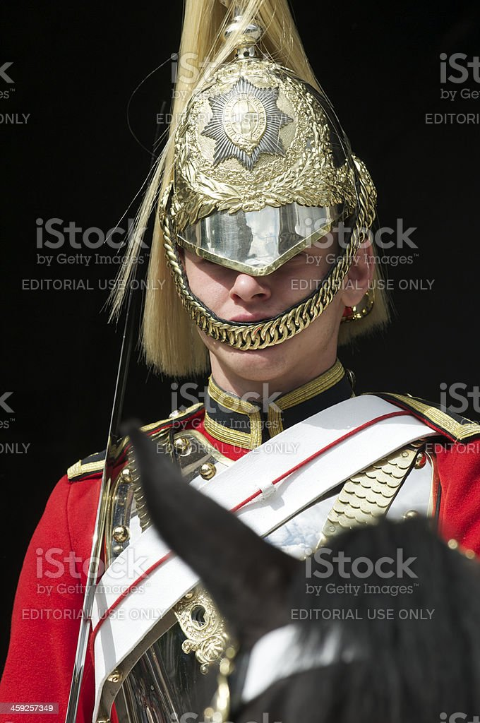 Guard in Red Uniform and Shiny Helmet Sits Horseback royalty-free stock photo