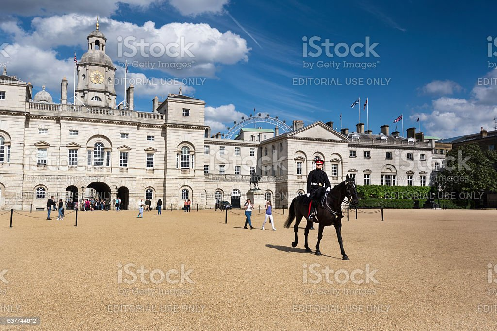 Guard rides horse across Horse Guards Parade London stock photo