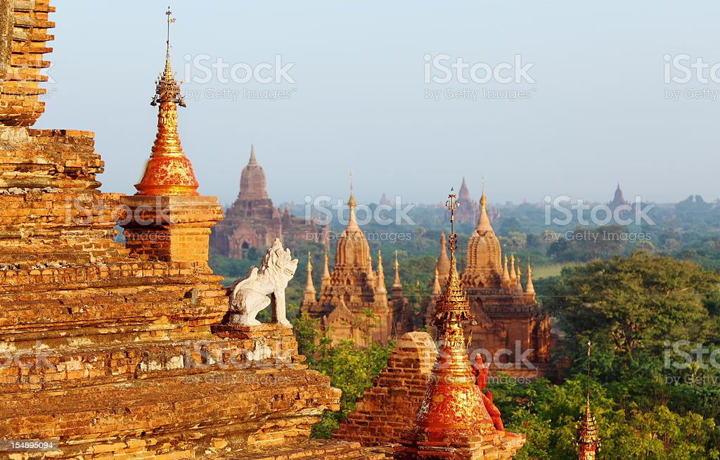 guard statue and Bagan temple field stock photo