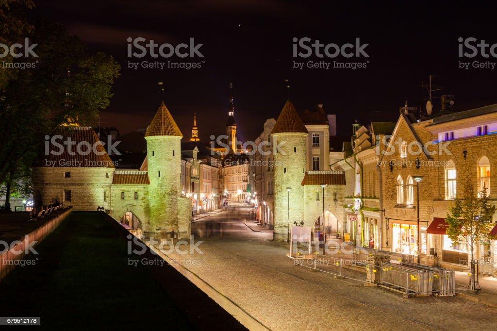 TALLINN, ESTONIA - 11 OKT 2015. Guard towers of Viru Gate, Narrow street illuminated of Old Town at night, City Hall on the background, Tallinn, Estonia stock photo