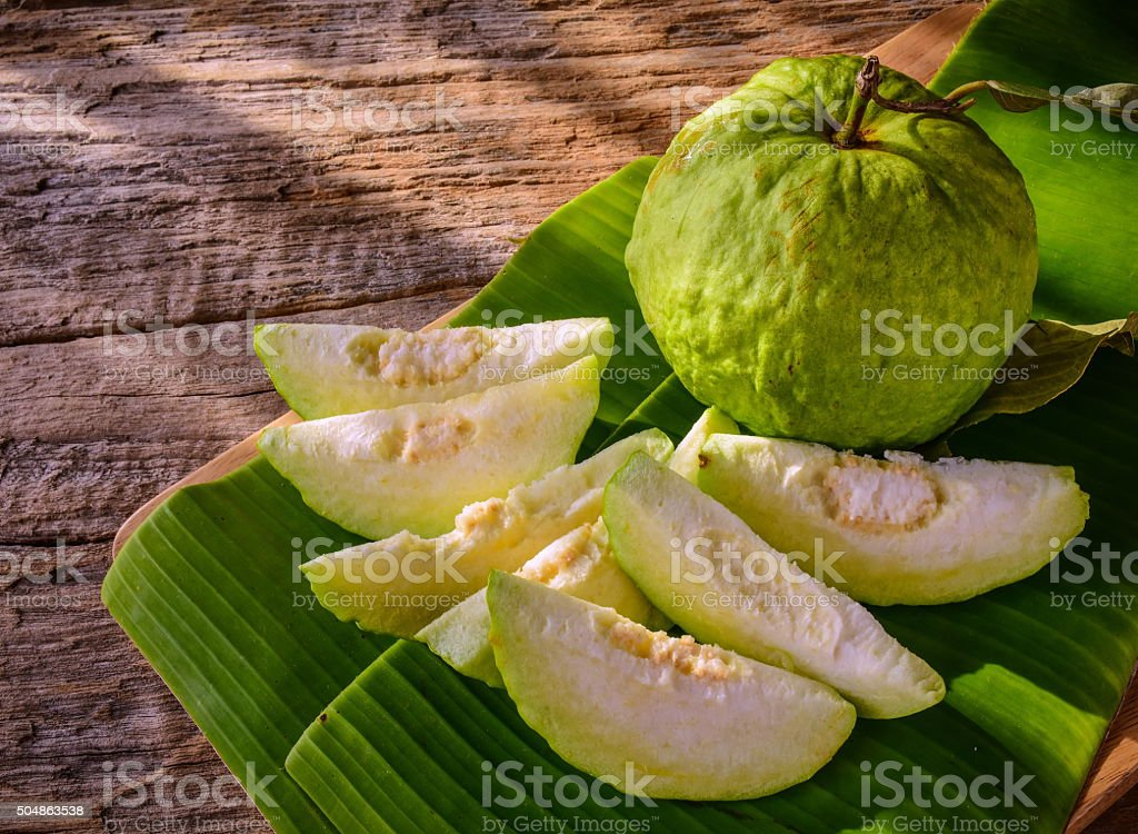 Guava.Fresh Guava on banana leaf and wood background. stock photo