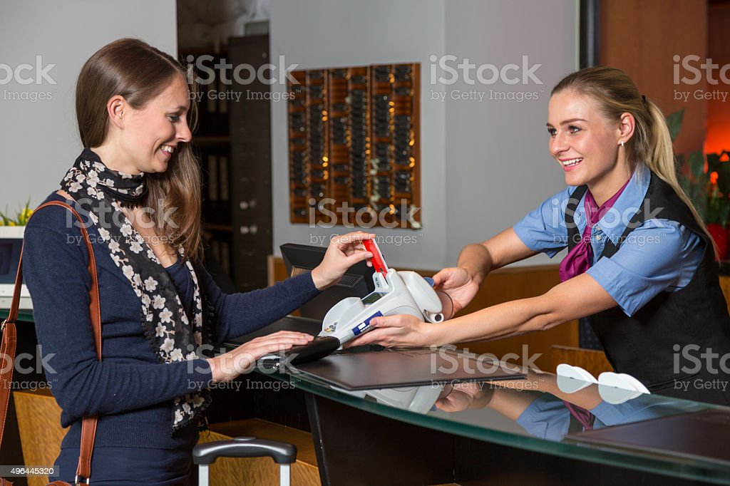Guest in hotel paying with credit card at reception stock photo