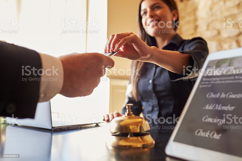 Guest takes room key card at check-in desk of hotel stock photo
