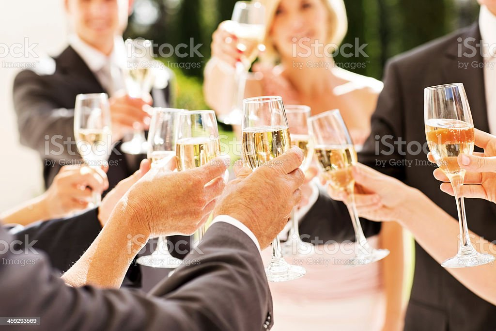 Guests And Couple Toasting Champagne Flutes At Reception stock photo