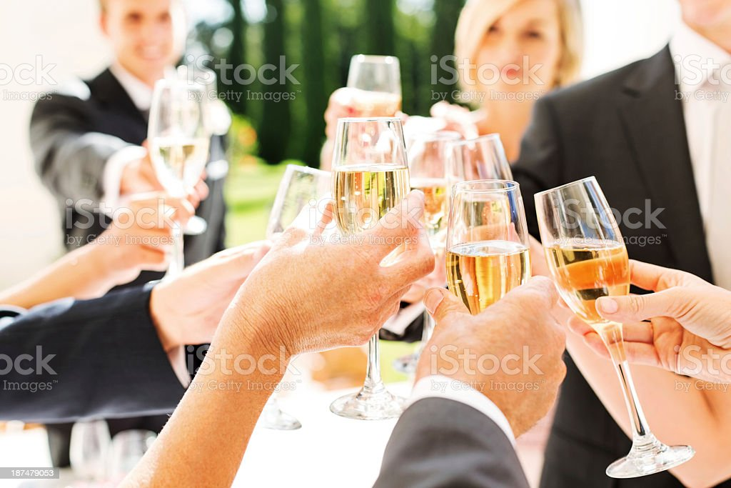 Guests And Couple Toasting Champagne Flutes At Wedding Reception stock photo