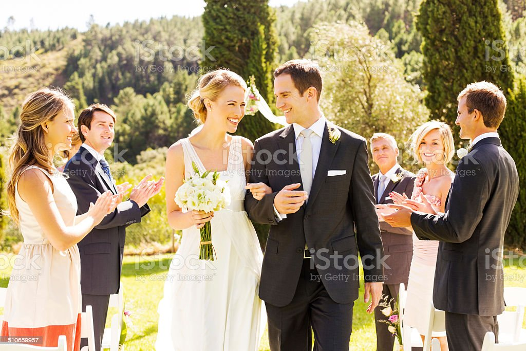 Guests Applauding While Looking At Newlywed Couple stock photo