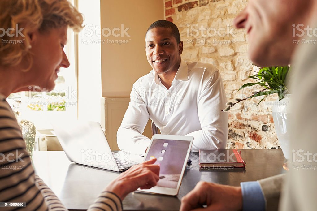 Guests checking in at a hotel using a tablet computer stock photo