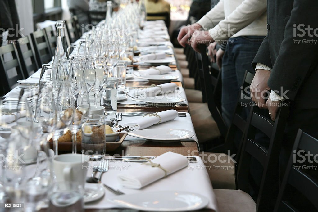 Guests in front of table set for dinner stock photo