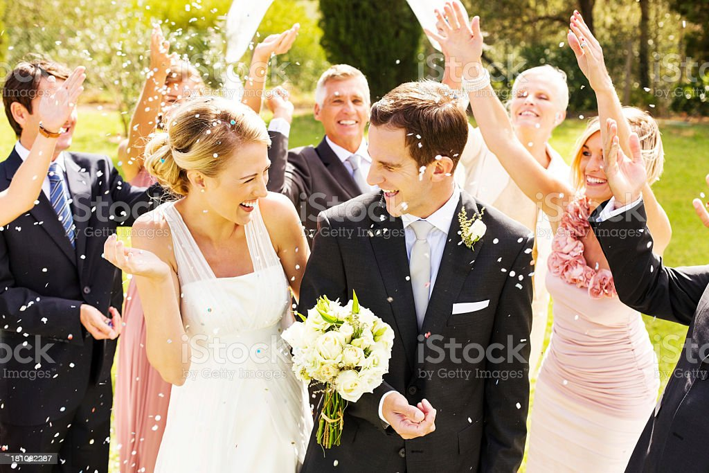 Guests Throwing Confetti On Couple During Reception In Garden stock photo