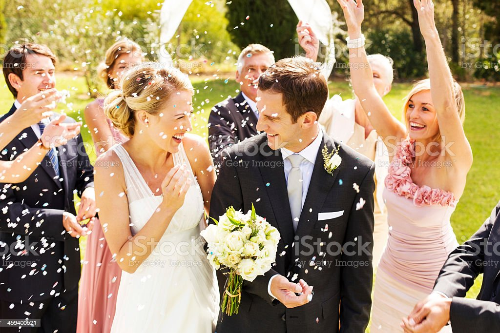 Guests Throwing Confetti On Couple During Wedding Reception stock photo