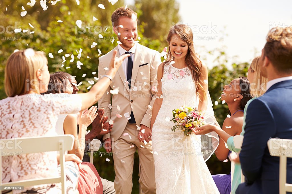 Guests Throwing Confetti Over Bride And Groom At Wedding stock photo