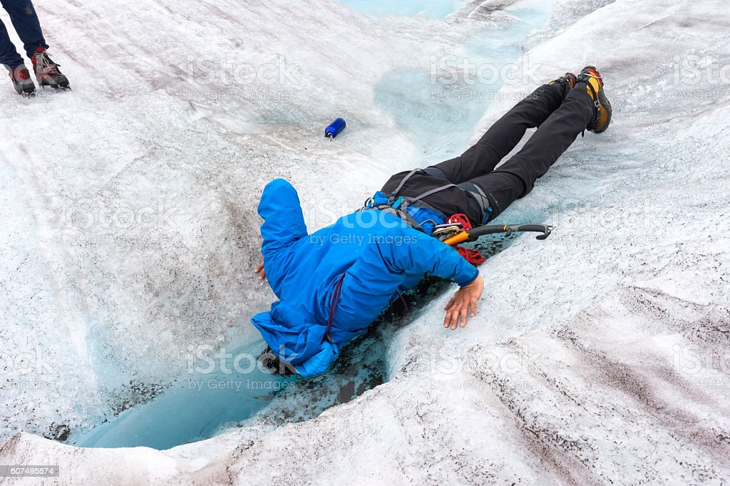 Guide dunks head into freezing glacier pool stock photo
