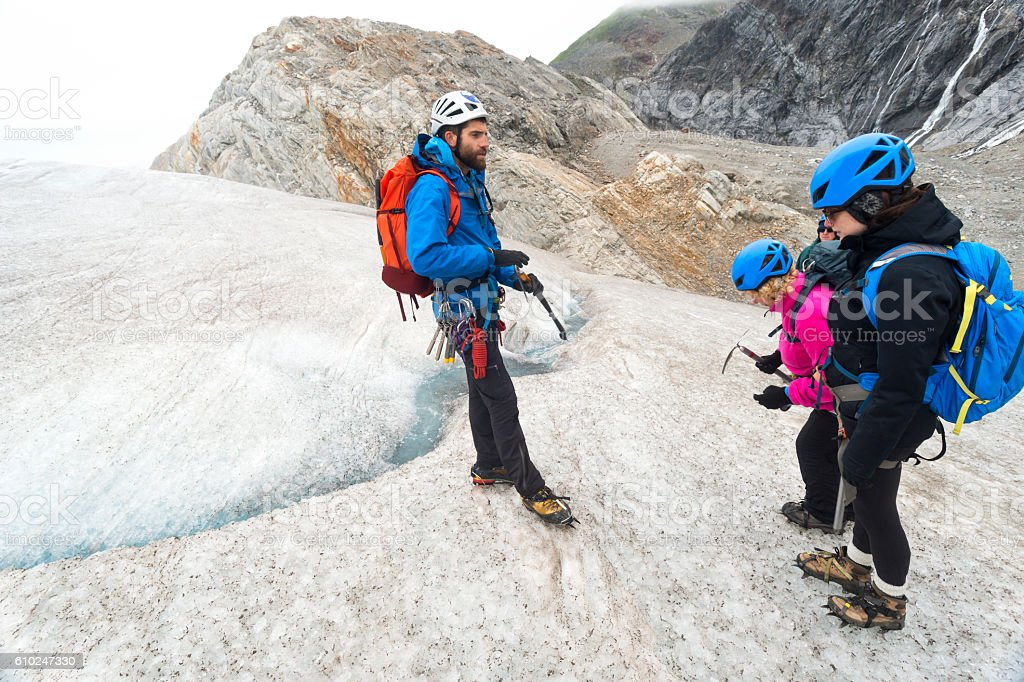 Guide instructs group about ice trekking stock photo