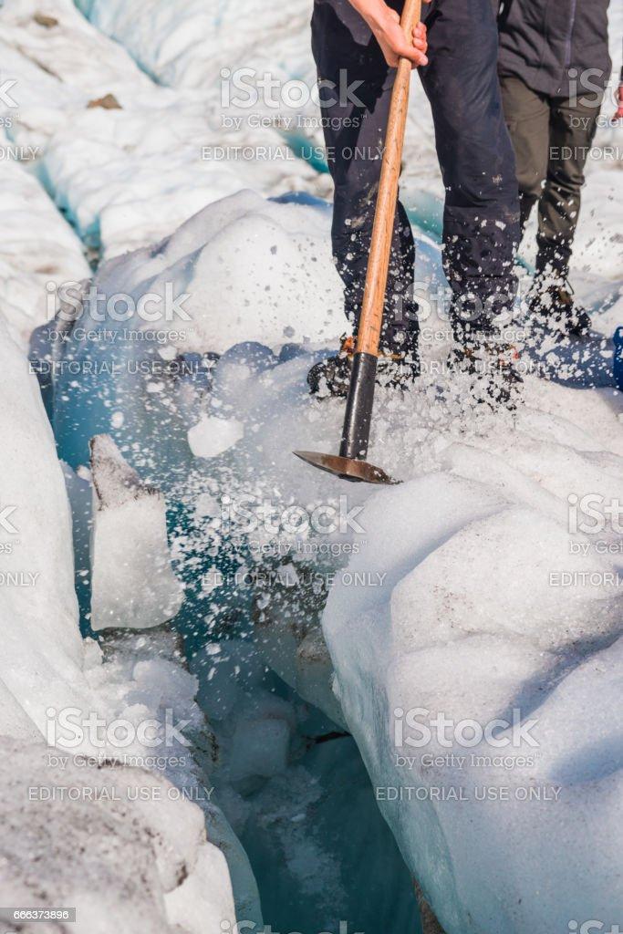 Guide to break the glaciers, Walking through glacier tunnel with guide using ice pick. Fox Glacier, New Zealand. stock photo