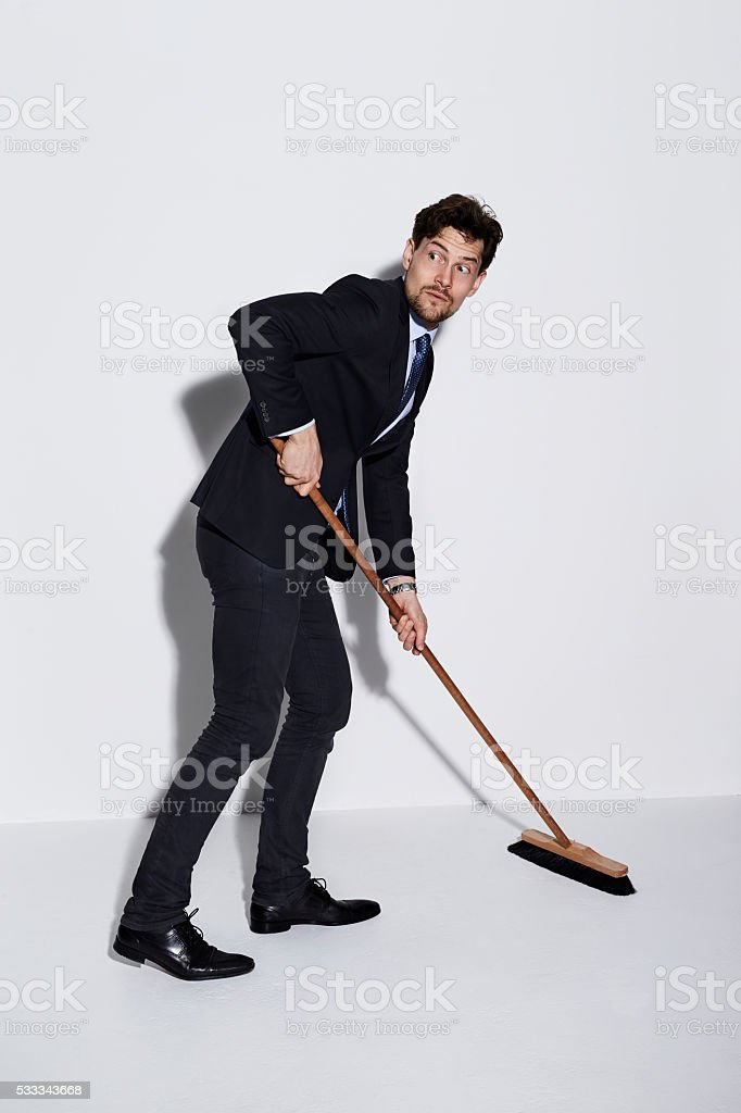 Guilty businessman sweeping in studio stock photo
