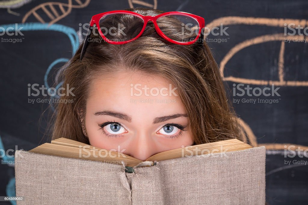 Guilty eyes of young student girl hiding behind a book stock photo