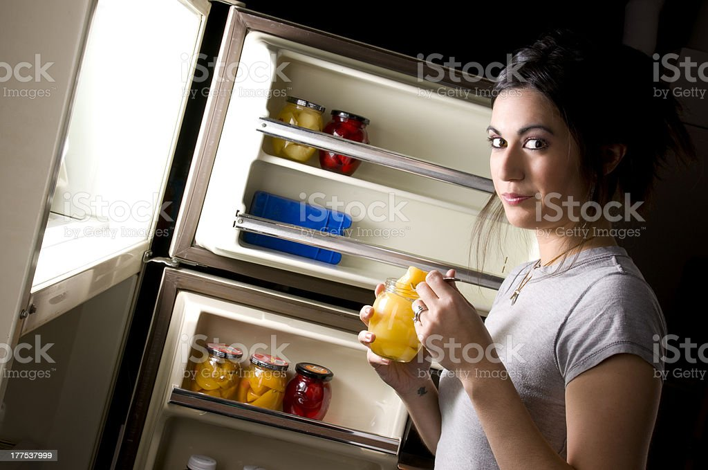 Guilty Female Caught Snacking on Peaches from Fridge Late stock photo