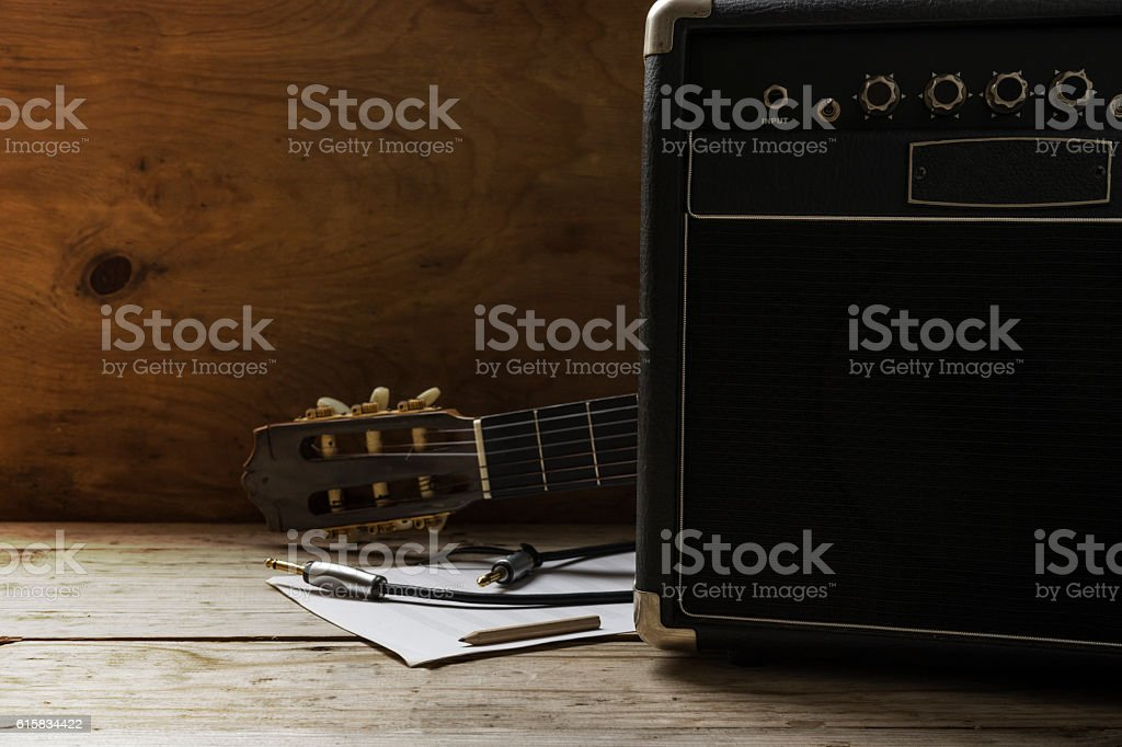 Guitar amplifier and guitar on wood table, light and shadow stock photo