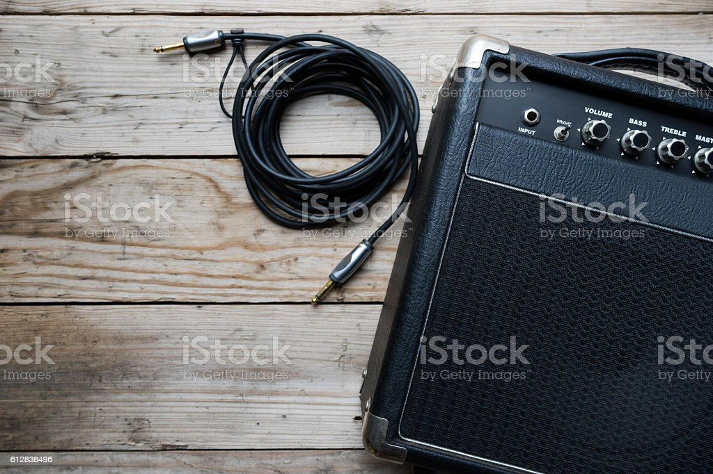 Guitar amplifier and guitar on wood table stock photo