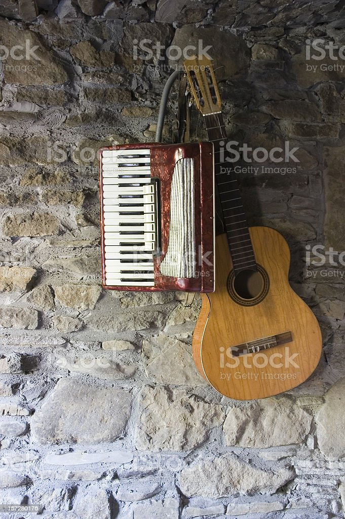 Guitar and accordion on the wall royalty-free stock photo