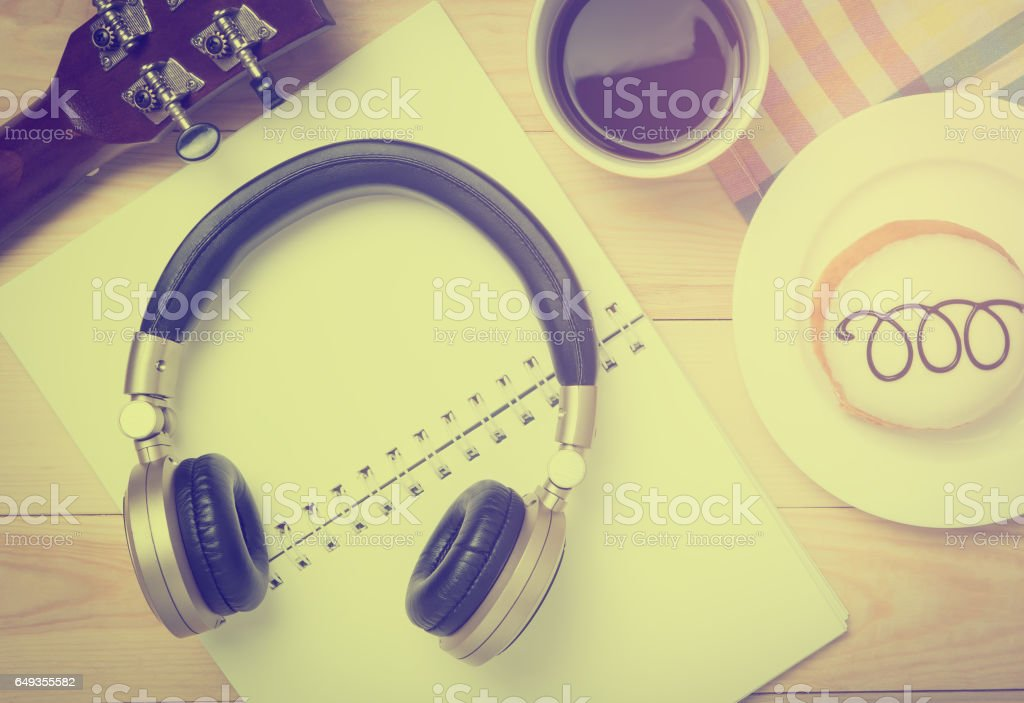 Guitar and music headphone on a cafe table stock photo