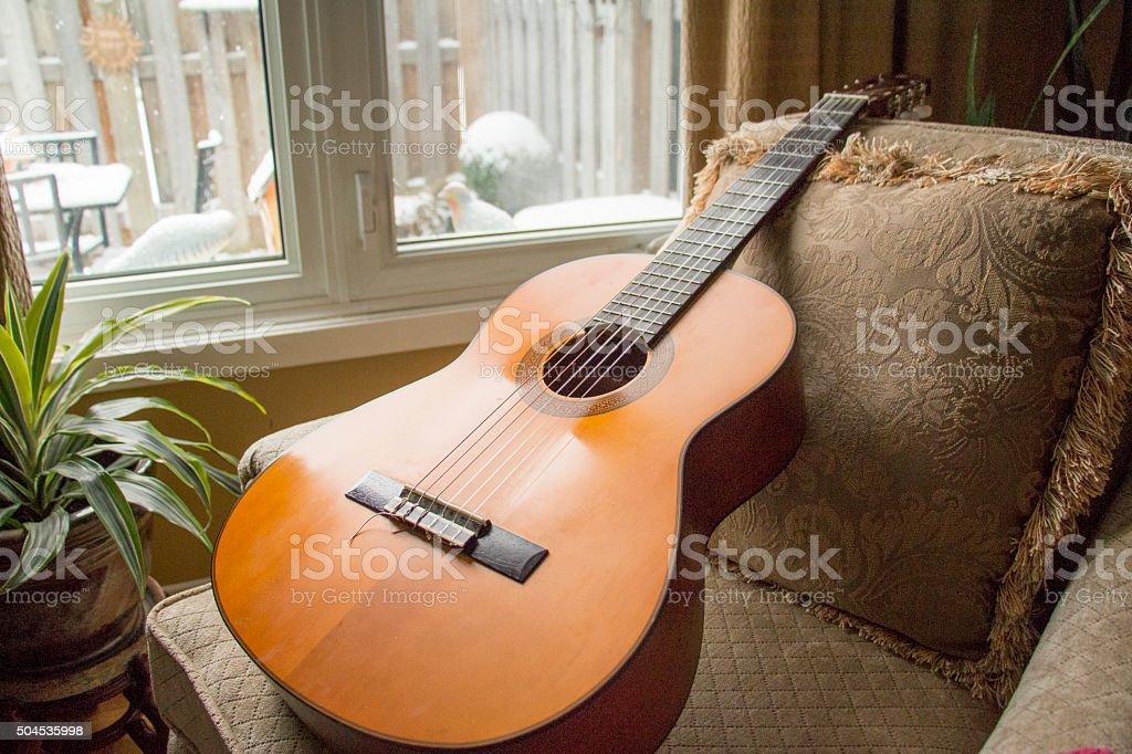 guitar by snowy window frame stock photo
