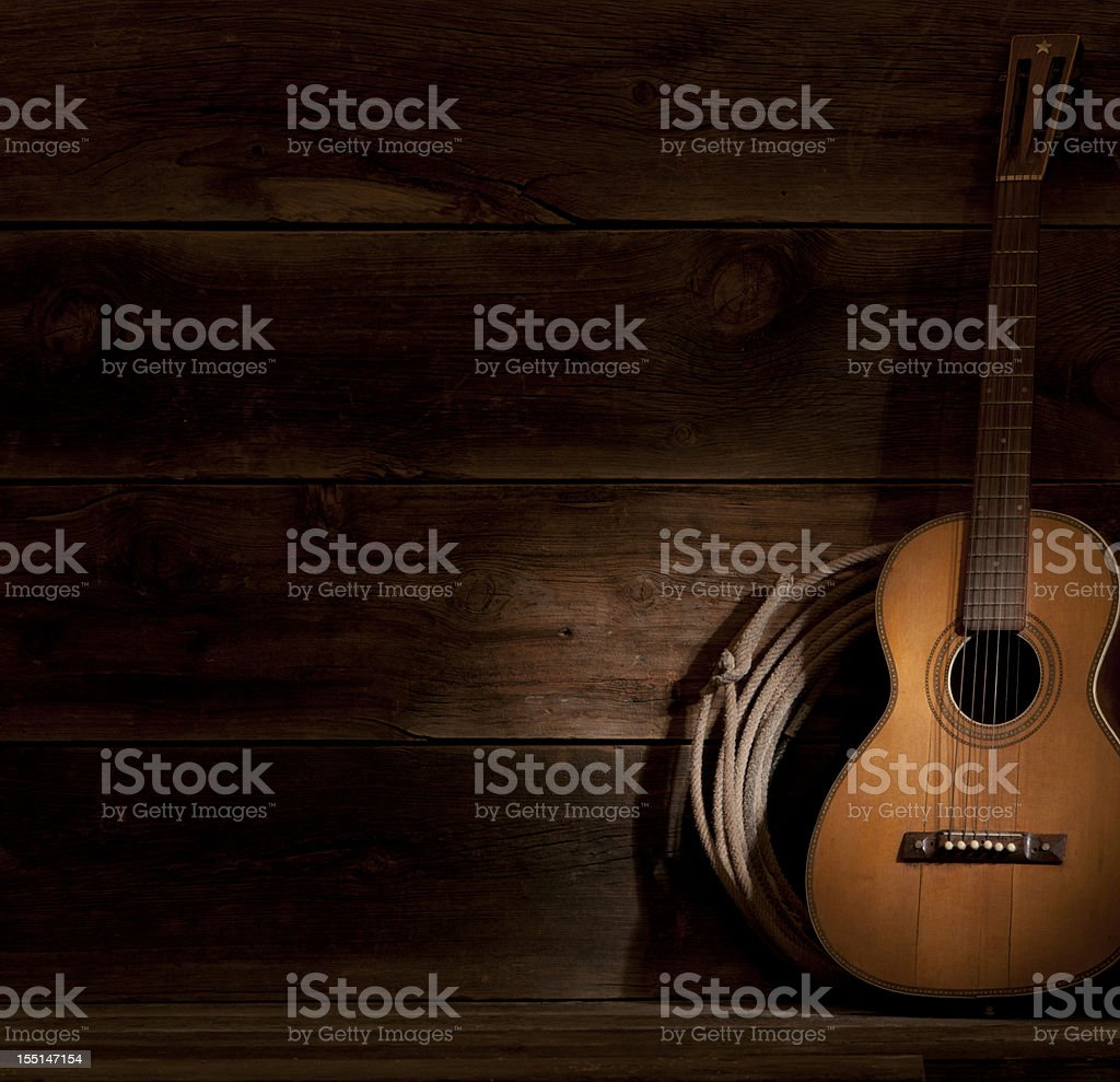 A guitar in the shadows, leaning against the wall royalty-free stock photo