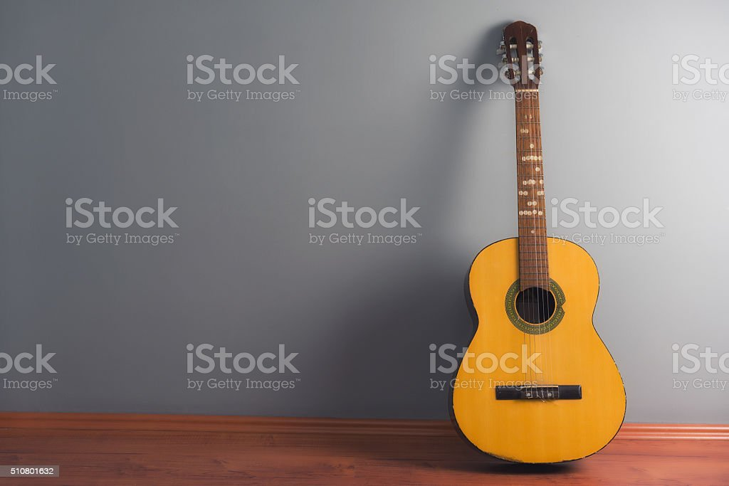 guitar leaning on gray wall stock photo