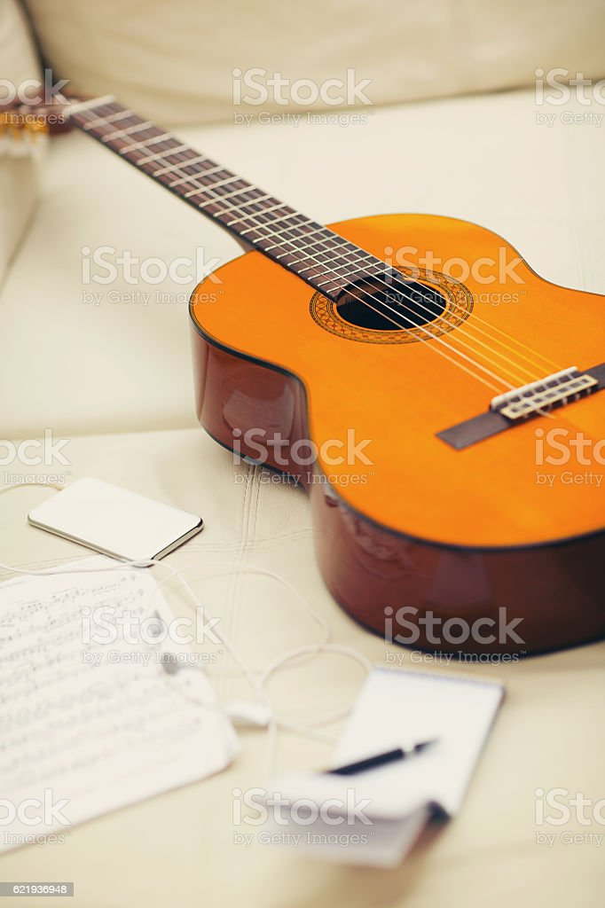 Guitar left on the sofa stock photo
