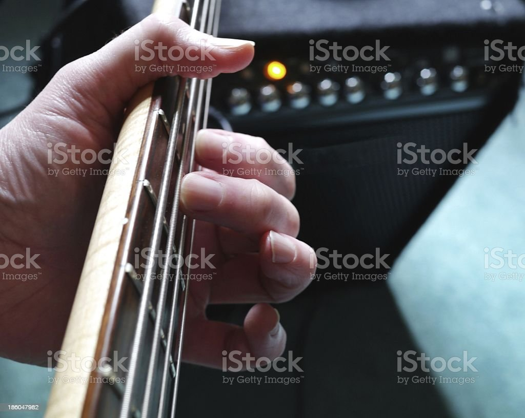 Guitar lesson with hand on strings and amplifier in background. stock photo