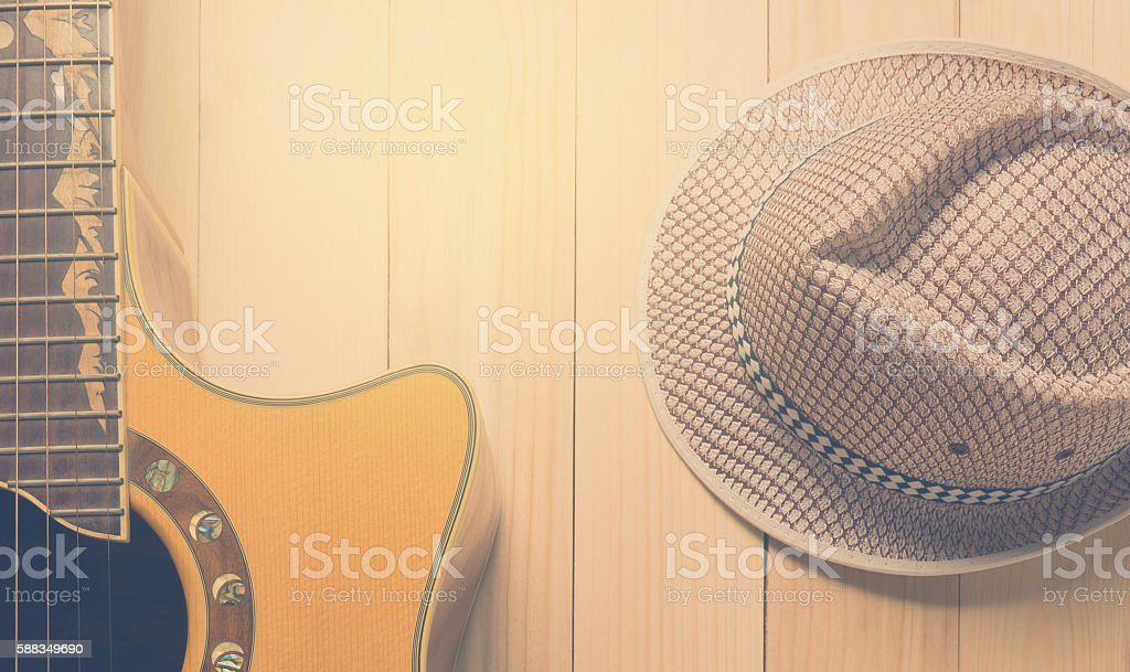 Guitar Music and summer hat on wooden background. stock photo