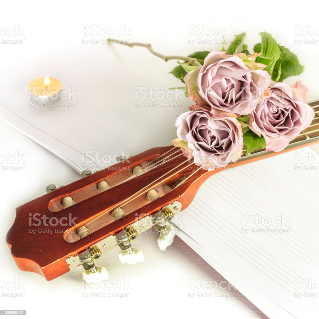 Guitar neck with roses and sheet music, on white stock photo