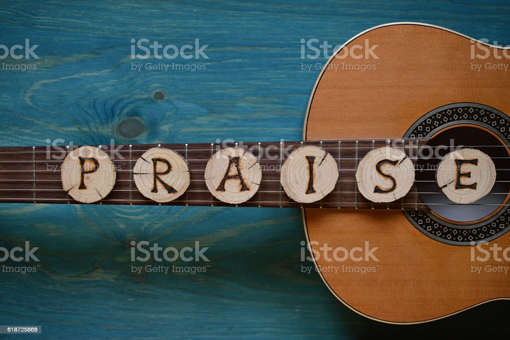 guitar on teal wood and the word: PRAISE stock photo