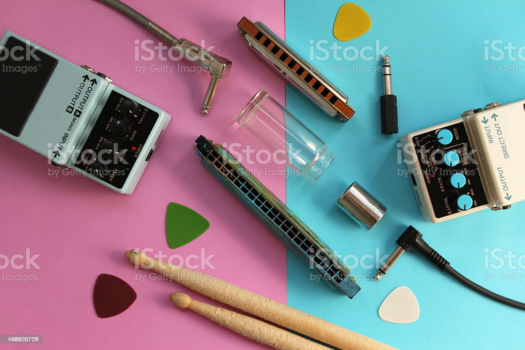 Guitar pedal, drum stick, harmonica, plug, guitar slide and pick stock photo