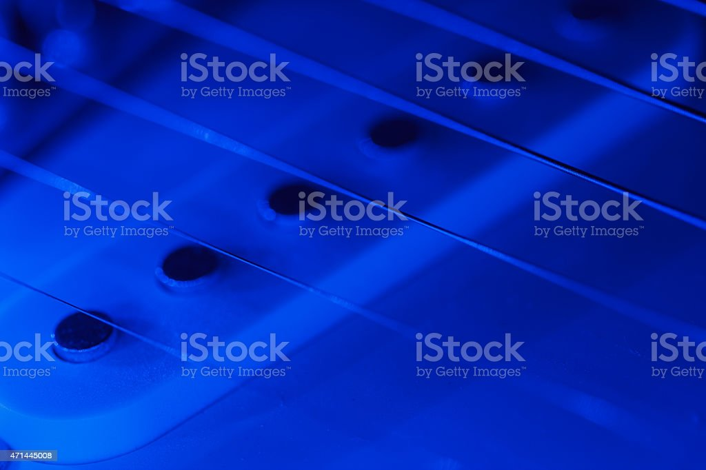 Guitar pickup and strings in blue light stock photo