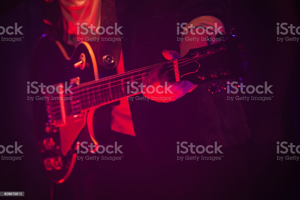 Guitar player on a stage with red light stock photo