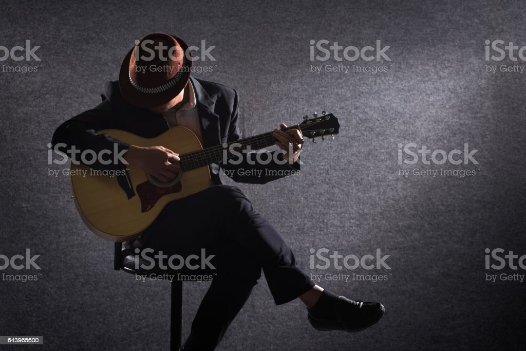 Guitar player on dark stock photo