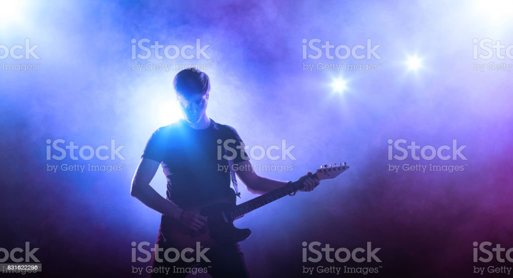 Guitar player on stage holding a guitar stock photo