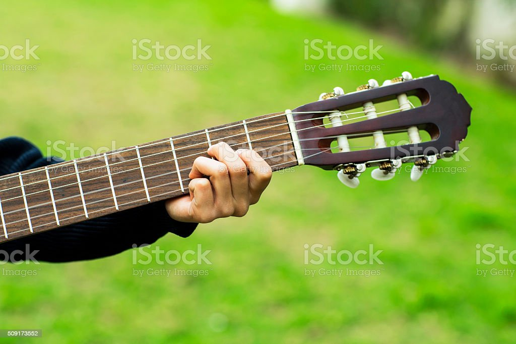 Guitar player playing song outdoor stock photo