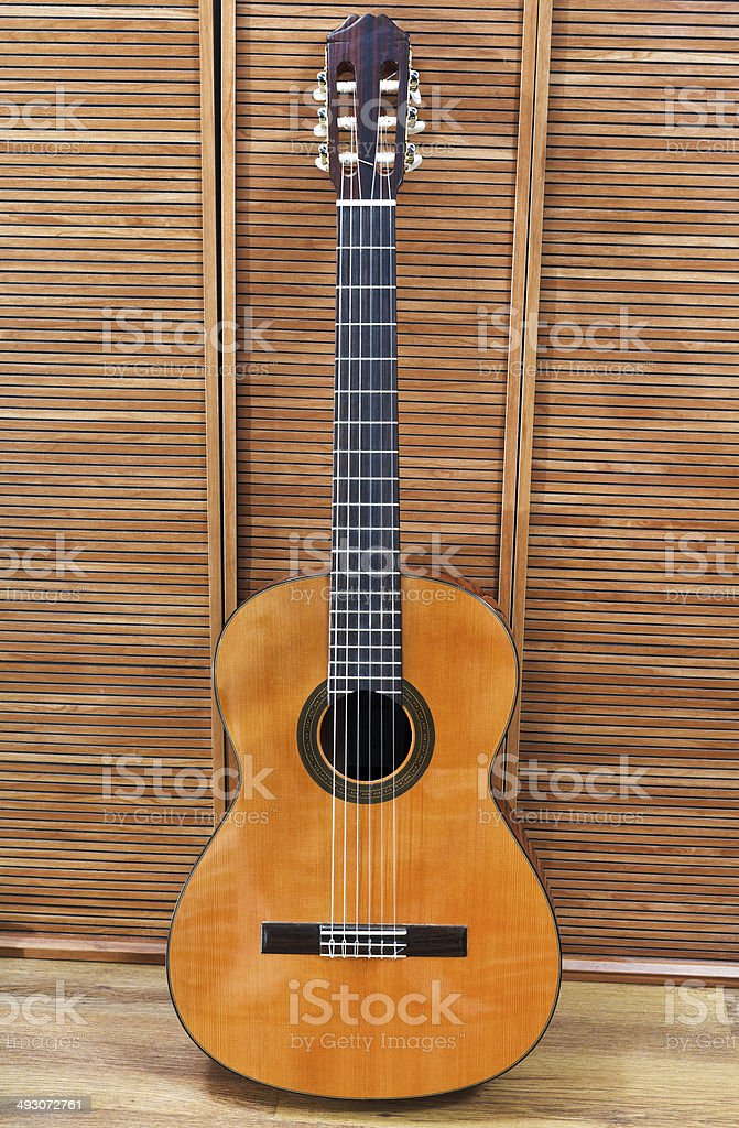 guitar stands at wooden wall stock photo