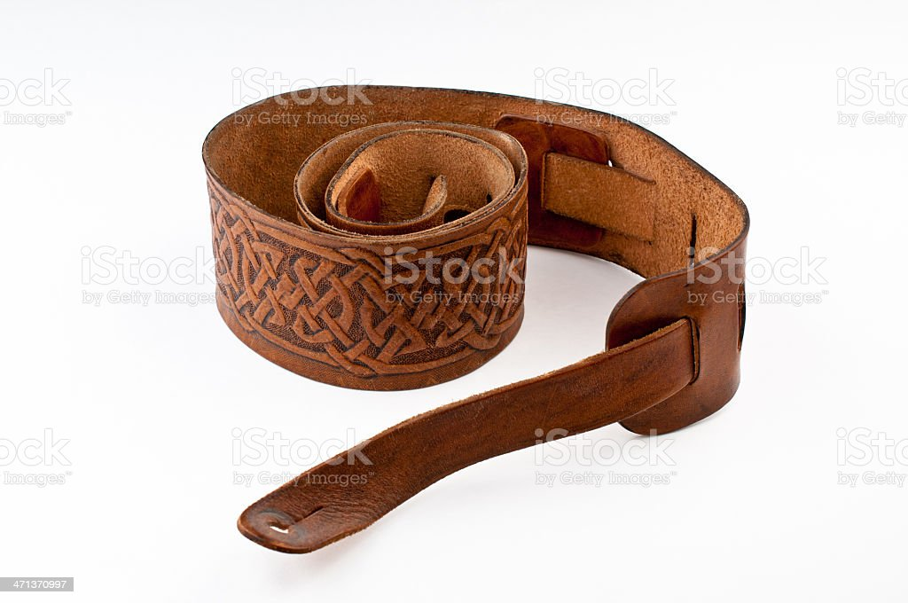 guitar strap leather brown celtic knotwork white background accessory stock photo