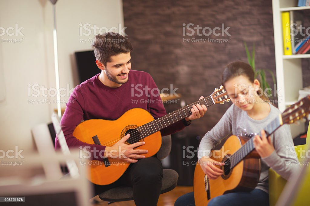 Guitar teacher teaching the little girl stock photo