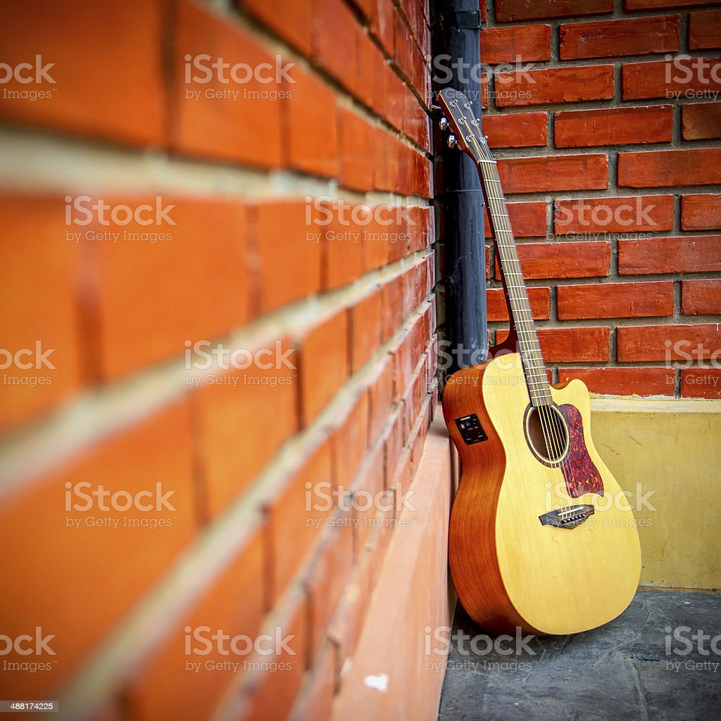 Guitar with red brick background. royalty-free stock photo