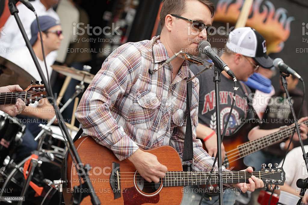 Guitarist and band play outside Hank's Saloon in Brooklyn stock photo
