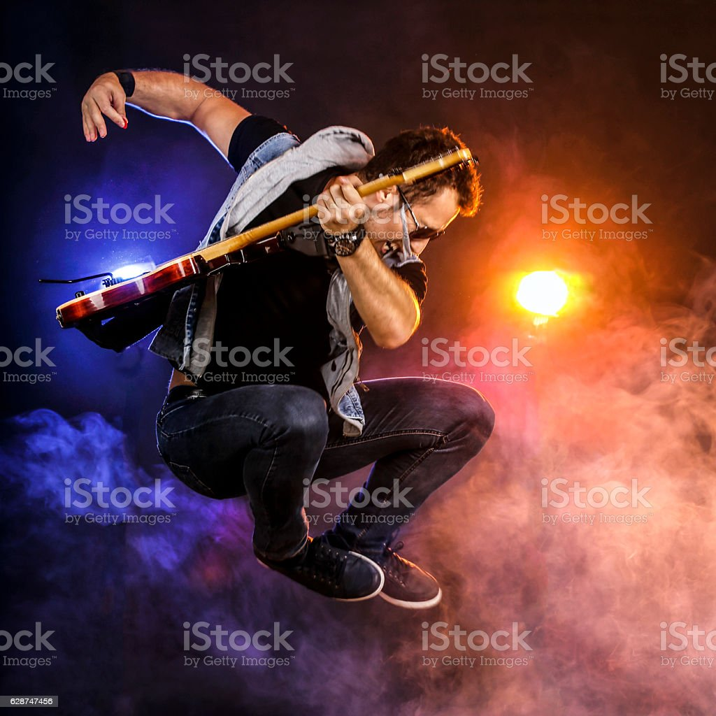 Guitarist jumping on stage stock photo