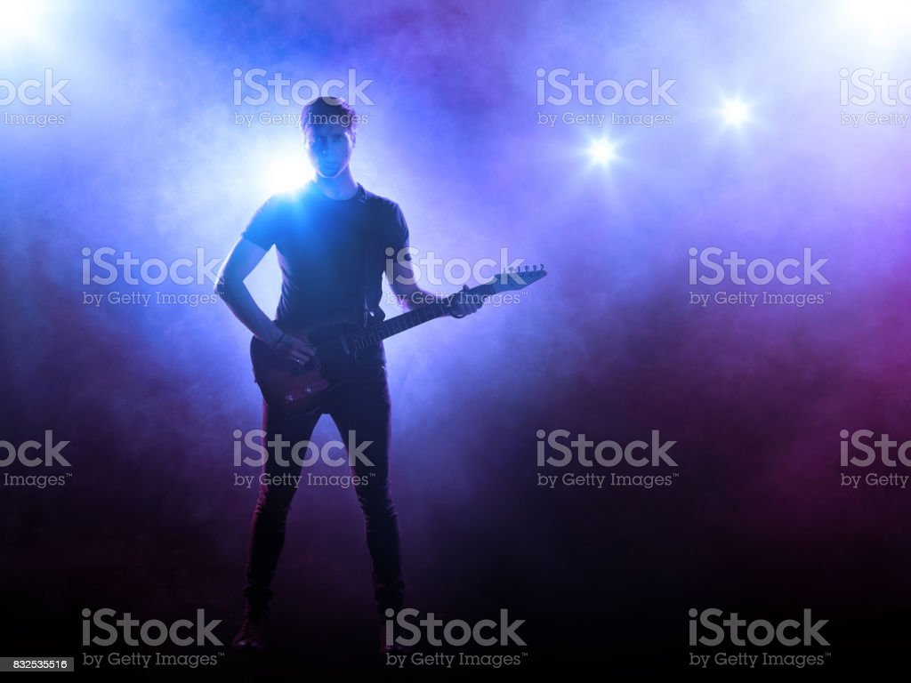 Guitarist playing a guitar in stage lights stock photo
