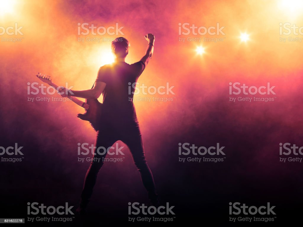 Guitarist playing a guitar on stage stock photo