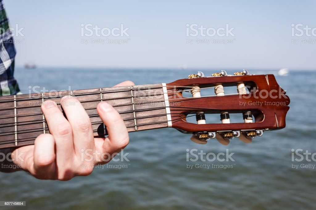 Guitarist playing next to sea. stock photo