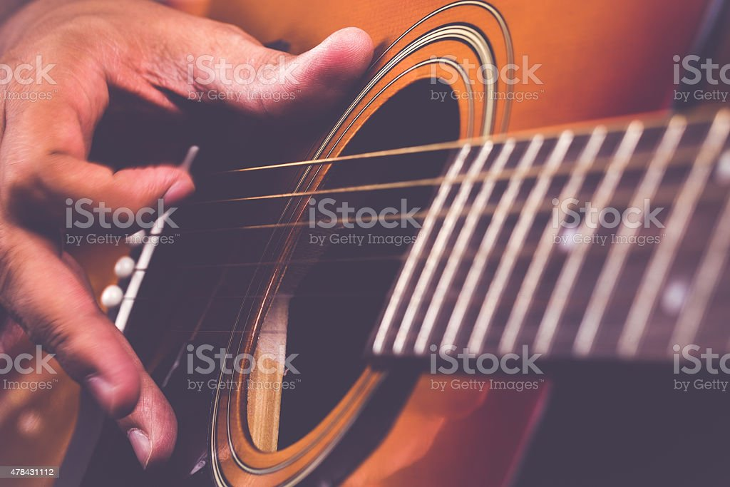 Guitarist Tending to his Instrument stock photo